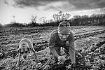 A farmer with his dog weeding the soil