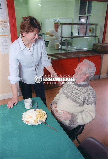 Elderly man in Salvation Army hostel eating meal and talking with member of staff,