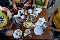 Rio de Janeiro lifestyle - people enjoy leisure time at sidewalk table in a typical Rio bar ( called barzinho ) - having chope ( draught beer or draft beer, beer served from a cask or keg ) and appetizers - fillet with onion, French fries and farofa, a toasted cassava flour mixture with butter, salt, olives, onions, garlic, hard boiled eggs, and/or bacon.