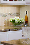 Detail shot of neutral-colored tile backsplash and granite countertops