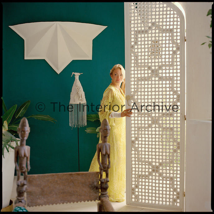 Liza Bruce poses beside one of the large latticed doors in the living room