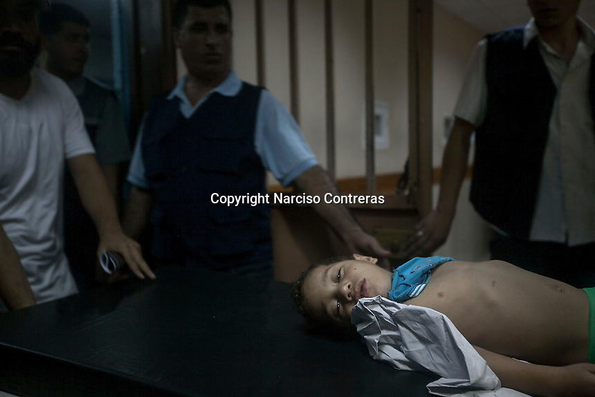 """August 22, 2014 - Gaza City, Gaza strip, Palestinian Territory: A Palestinian child is wheeled from the emergency ward at Al-Shifa hospital after he was injured during an airstrike in Al-Sabra neighbofhood as """"Protective Edge"""" Israeli military operation continues in the Gaza strip. (Narciso Contreras/Polaris)"""