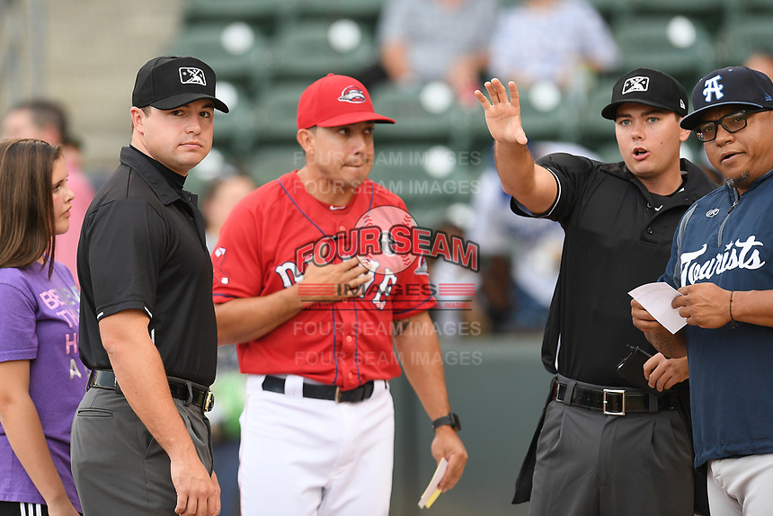 First base umpire Colin Baron, left, with home plate umpire Adam Clark work a game between the Greenville Drive and the Asheville Tourists on Friday, August 23, 2019, at Fluor Field at the West End in Greenville, South Carolina. At center is Drive manager Iggy Suarez. At far right is Asheville manager Roninson Cancel. Greenville won, 11-1. (Tom Priddy/Four Seam Images)