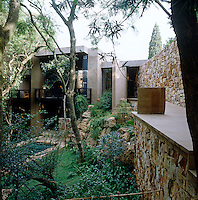 Pots by artist Dina Prinsloo bisect the walkway to the house along a terraced stone wall