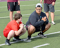 Graham Thomas/Herald-Leader<br /> Siloam Springs football player Marco Salcedo, right, demonstrates a stretching drill to a Panther Academy participant on June 11 at Panther Stadium.