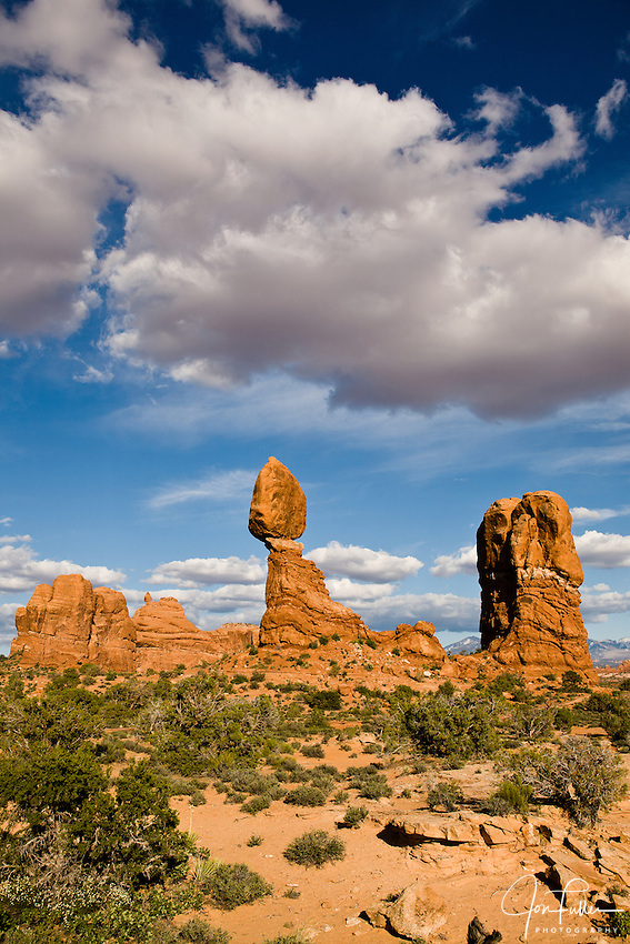 Cumulus clouds in blue skies over Balanced Rock in Arches National Park, Moab, Utah, USA.