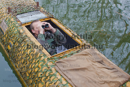 Nature photographer Bence Mate from Hungary presents his floating watch cover he uses to approach birds in the wild in Budapest, Hungary on December 12, 2011. ATTILA VOLGYI