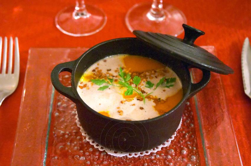 Carcassonne. At the Restaurant Auberge des Lices. Languedoc. Black cast iron pot with lid used for serving a pumpkin soup, soupe de potiron. France. Europe.