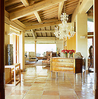 Between the rustic beams of the roof and the polished surface of the terracotta tiled floor the open-plan living room is furnished with an assortment of pieces which span the centuries