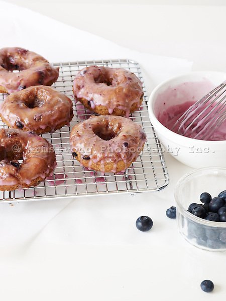 Fresh blueberry doughnuts cooling on a metal rack in a home kitchen. With bowl of icing, whisk, and cup of blueberries.
