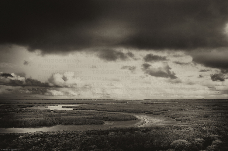 Blakeney marshes in north Norfolk England on a wild spring day with storm clouds