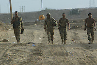 Iraqi tankers from the 1st company, 1st armour battalion of the 1st mechanized Iraqi Army Brigade walk to their base after dismounting from their tank while conducting  patrols, check points and observation posts on code name route Michigan, the main road of Ramadi in the week during the national election on TUE Dec 13 2005 in Ramadi, Iraq. 1st company is part of the first armor battalion of the New Iraqi Army. it has started its training in January 2005. after 50 days their 35 russian and chinese built T 55 tanks begun conducting operations under the guidance of a US military adivisor team. in April 2005 they patrolled in the Abu Ghraib area concluding their first significant mission. While these old tanks are rolling on the ramadi streets more modern T72s are getting ready to become fully operational in Taji, their main base. the Iraqi army wanted to show their power in ramadi during the Dec 15 elections displaying their new armour company. but like all the other Iraqi forces they are not going to secure the polling sites, staying in the rear with the rest of the iraqi and coalition forces. T 55s are very old tanks. production begun in the late 50s to the late 70s. athough obsolete many countries still use the T55 as their main heavy armoured combat vehicle. slow, heavvy and with very little room for the crew it suffers from many mechanical problems constantly challenging the iraqi mechanics and engineers.