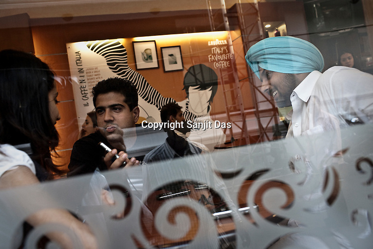 Youngsters are seen chilling out at an upmarket cafe in New Delhi, India. Photo: Sanjit Das