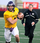 SIOUX FALLS, SD - APRIL 28: Quarterback Calvin Jacobson #4 of the University of Sioux Falls scrambles out of the pocket while head coach Jed Stugart pursues during the Cougars spring scrimmage Saturday evening at Bob Young Field. (Photo by Dave Eggen/Inertia)