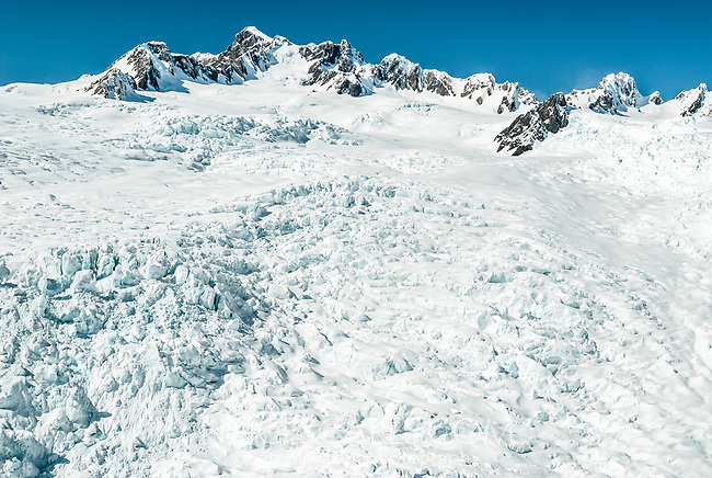 Heavily crevassed Explorer Glacier in upper part of Fox Glacier. Sharp peak of Dougles Peak on skyline, Westland Tai Poutini National Park, West Coast, UNESCO World Heritage Area, New Zealand, NZ