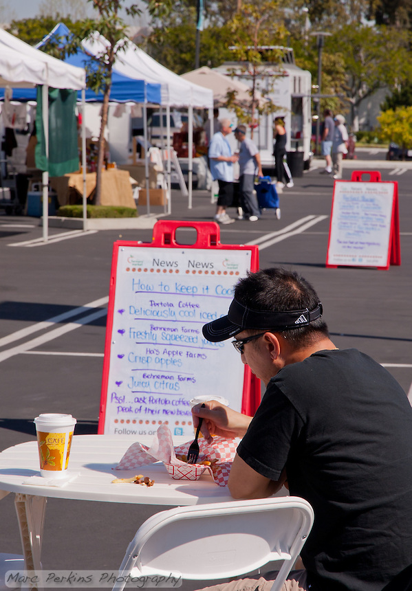 A view down the entire length of South Coast Collection's farmers market, with an unidentified man eating in front.