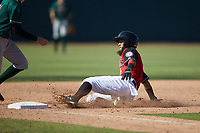 Miguel Aparicio (5) of the Hickory Crawdads slides into third base during the game against the Greensboro Grasshoppers at L.P. Frans Stadium on May 26, 2019 in Hickory, North Carolina. The Crawdads defeated the Grasshoppers 10-8. (Brian Westerholt/Four Seam Images)