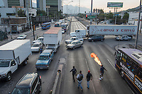 "Jesus Aleman from the ""13"" gang earns a living by blowing fire at the traffic lights. Monterrey, Nuevo Leon, Mexico"