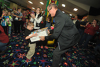 NWA Media/Michael Woods --12/20/2014-- w @NWAMICHAELW...Springdale fire chief Mike Irwin helps Colt Bell, age 8 of Springdale, with his gifts Saturday morning at Lokomotion Family Fun Center during the Springdale firefighters annual Christmas event for local children.  Springdale firefighters treated the kids with food, rides, games, and gifts from Santa.