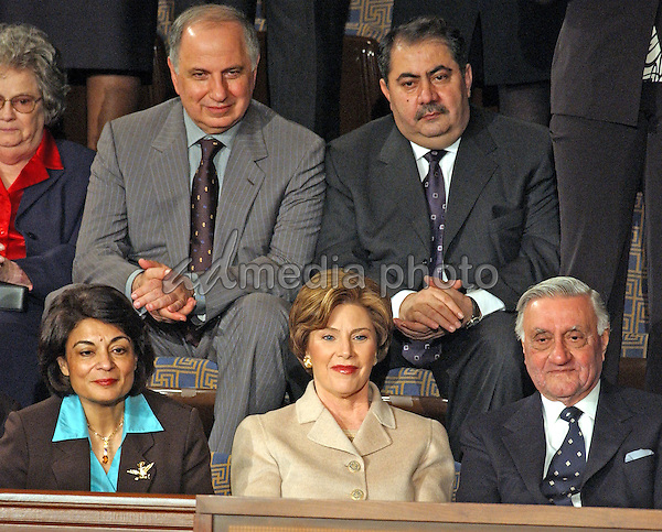 FILE PHOTO: In this file photo from January 20, 2004, first lady Laura Bush sits with invited guests from the Iraqi Governing Council for her husband, United States President George W. Bush's 2004 State of the Union Address to a Joint Session of the United States Congress at the Capitol in Washington, D.C. on January 20, 2004.  Left to right in the top row: Doctor Ahmed Chalabi, Iraqi Governing Council; and Hoshyar Zebari, Iraqi Interim Foreign Minister.  Left to right on the bottom row: Ms. Rend al-Rahim, Iraqi Senior Diplomatic Representative; first lady Laura Bush; and Doctor Adnan Pachachi, President, Iraqi Governing Council.  Iraqi state media reported Chalabi passed away from a heart attack on November 3, 2015.  He was in his early 70s. Photo Credit: Ron Sachs/CNP/AdMedia