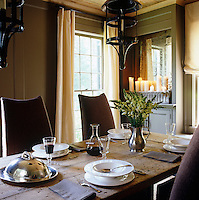 Candlelight reflected in the custom made mirror adds a touch of romance to this understated dining room