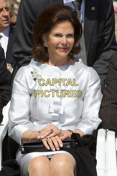 QUEEN SILVIA OF SWEDEN.Inauguration of Countess Sonja Statue  on the 100th Birthday of Count Lennart Bernadotte af Wisborg, Island Mainau in Lake Constance..May 8th, 2009.ceremony half length white silver dress silk satin sitting royal royalty   .CAP/PPG/JH.©Jens HartmannPeople Picture/Capital Pictures