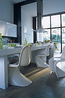 White Verner Panton chairs stand on a polished concrete floor around a white dining table laid with green glassware