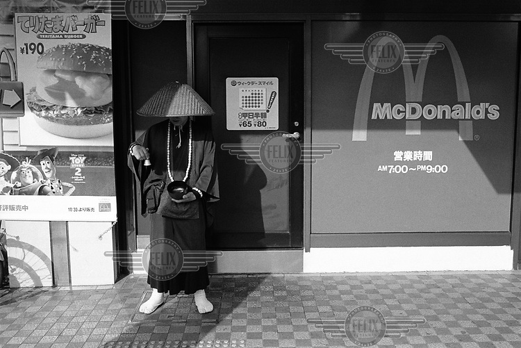 Japanese Buddhist monk collecting alms next door to a McDonald's restaurant.