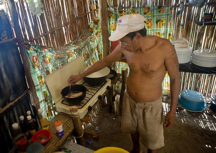 A local Kuna man cooks fresh jackfish in oil on Isla Pelikano, San Blas Islands, Kuna Yala, Panama