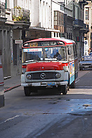 A local old Mercedes bus on a street in the city to the Old Town Ciudad Vieja, painted in red and grey Montevideo, Uruguay, South America
