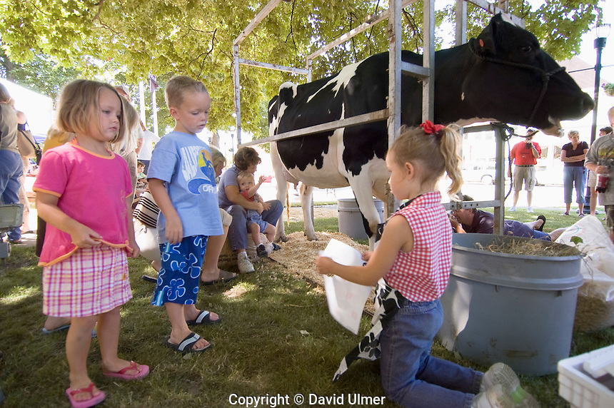 Three girls at milking booth at Dairy Days, Greenville, IL....