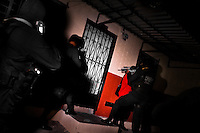 Policemen from the special anti-gang unit (Unidad Antipandillas) enter the apartment of an alleged gang member during the night in a gang neighbourhood of San Salvador, El Salvador, 13 December 2013. Although the murder rate in the country has dropped significantly, after a truce between two major street gangs (Mara Salvatrucha and Barrio 18) was agreed in 2012, the lack of security and violence are still the main issues in people's daily life. Due to the fact the gangs have never stopped their criminal activities (extortions, distribution of drugs and kidnappings), the Police anti-gang forces keep running their operations and chasing the 'homeboys' (how the gang's foot soldiers usually call themselves) in the poor, socially deprived suburbs of Salvadoran cities.