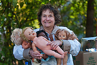 Susie Rasmussen holds four of the dolls she bought at an estate auction...The contents of a home on East Broadway went before the auction block Saturday. ..Eager bargain hunters took their time looking over prospective purchases hoping others didn't know of its true value or weren't interested in their item of choice...Many boxed items were sold with the buyer only interested in one item in the box of interest. Many buyers bought large lots of glass and pottery for a single knickknack in the collection.