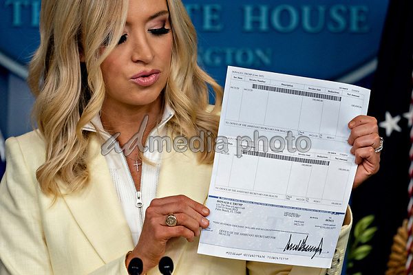 White House Press Secretary Kayleigh McEnany, holds a check, in the amount of United States President Donald J. Trump's annual salary, to be donated to the U.S. Department of Health and Human Services (HHS) during a news conference in the Brady Press Briefing Room of the White House in Washington, D.C., U.S., on Friday, May 22, 2020. Trump ordered states to allow churches to reopen from stay-at-home restrictions imposed to combat the coronavirus outbreak, saying he would override any governor who refuses. <br /> Credit: Andrew Harrer / Pool via CNP/AdMedia