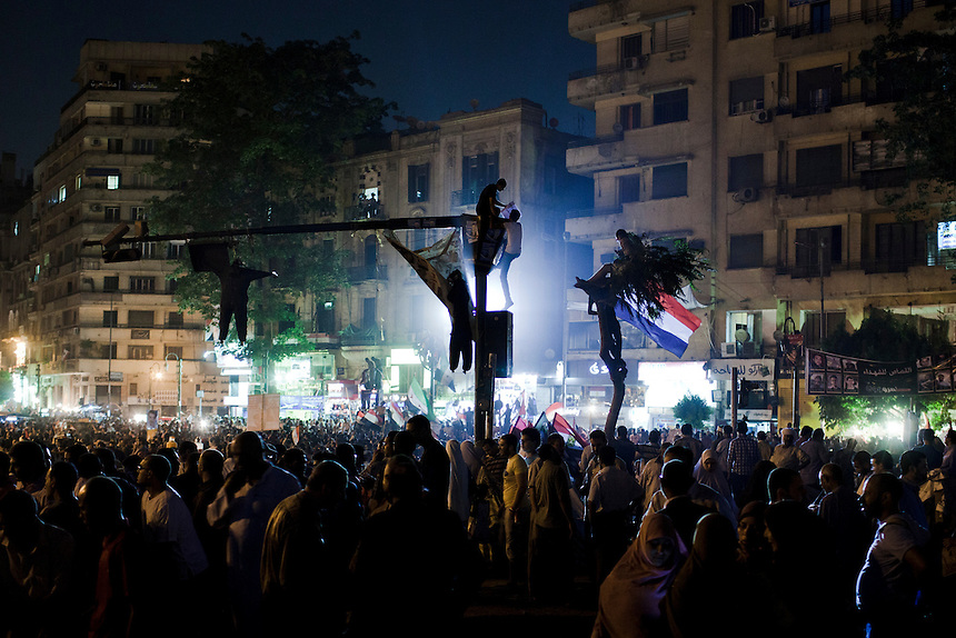 Egyptian demonstrators stand atop a light pole during a protest in Cairo's Tahrir Square against the continued presidential campaign of Hosni Mubarak's final Prime Minister, Ahmed Shafiq, June 3, 2012. Photo: ED GILES.