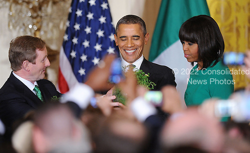 United States President Barack Obama accepts a bowl of shamrocks from Prime Minister Enda Kenny of Ireland as first lady Michelle Obama looks on during a reception in the East Room of the White House in Washington, D.C., March 19, 2013 in Washington, DC. <br /> Credit: Olivier Douliery / Pool via CNP
