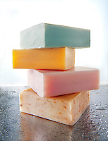 4 bars of scented hand made soaps piled on an aluminium background with water droplets