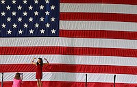 A woman poses in front of a large American flag after a speech made by President Barack Obama at the nTelos Wireless Pavilion in Charlottesville, VA.