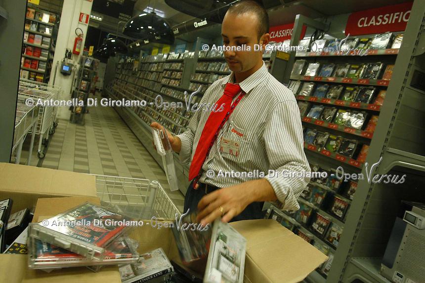 Supermercato Coop. Coop supermarket..Commesso aziona il sistema antitaccheggio ai dvd..Sales assistant operates the antitheft system to the dvd....