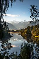 Sunrise over Lake Matheson and Southern Alps, with Mt. Tasman and Aoraki Mt. Cook on horizon, Westland Tai Poutini National Park, West Coast, South Westland, UNESCO World Heritage Area, New Zealand, NZ