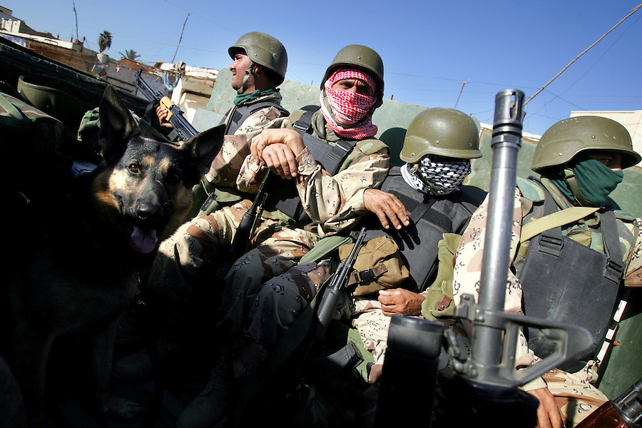 Iraqi security forces accompanied by a Marine working dog pass through the streets of Ramadi on Thurs. December 23, 2004.