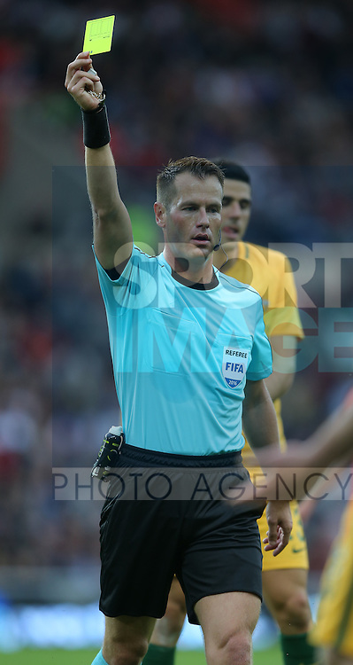 Referee Danny Makkelie issues a yellow card during the International Friendly match at the Stadium of Light, Sunderland. Photo credit should read: Simon Bellis/Sportimage