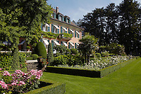 The well-tended flowerbeds are filled with rose bushes and framed with clipped box hedges