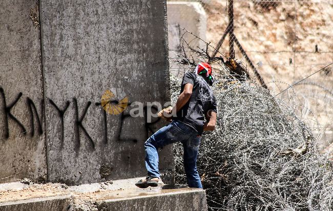 Palestinian protester hurls stones at Israeli soldiers during a weekly demonstration against  Israel's controversial separation barrier in the West Bank village of Nilin on June 1, 2012. When completed, 85 percent of the wall will have been built inside the West Bank, taking land from Palestinian villages like Bilin and Nilin. Photo by Ahmed Mesleh