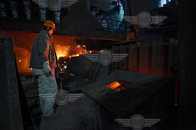 Workers operate near the iron smelter at Ma Steel's new plant at night in Maanshan.