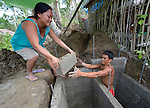 Eirene Macalalad hands a cement block to her husband Imarito as he constructs a septic tank at their home in Bacubac, a seaside neighborhood in Basey in the Philippines province of Samar that was hit hard by Typhoon Haiyan in November 2013. The storm was known locally as Yolanda. Norwegian Church Aid, a member of the ACT Alliance, is sponsoring the construction of bathrooms with septic systems for houses in the village where existing systems were destroyed by the typhoon's unusually high storm surge.