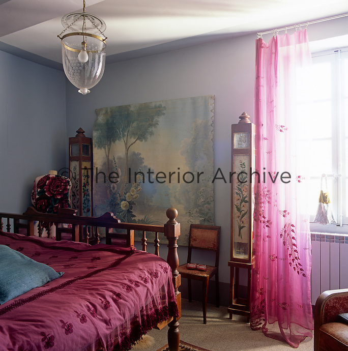 A blue bedroom with a pink sheer curtain hanging at the window. A glass pendant light hangs above a wooden double bed has a deep pink cover.