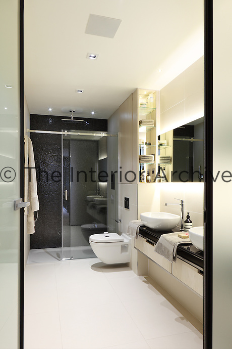 A view into a stylish luxury bathroom with double washbasins on a drawer unit. The bathroom has a tiled shower area with a glass sliding door.