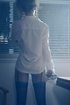 Back of a sexy woman wearing a white men's dress shirt and black stockings looking out of the window at night Image © MaximImages, License at https://www.maximimages.com
