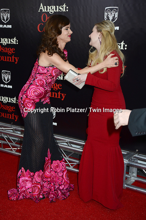 "Juliette Lewis in Naaen Khan pink flowered embroidered dress and Abigail Breslin attend the New York Premiere of ""August: Osage County"" on December 12, 2013 at the Ziegfeld Theatre in New York City."